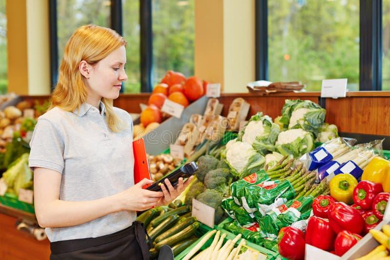 妇女在有数据注册终端的超级市场 免版税图库摄影