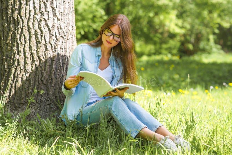 妇女在有杂志的公园 免版税库存图片