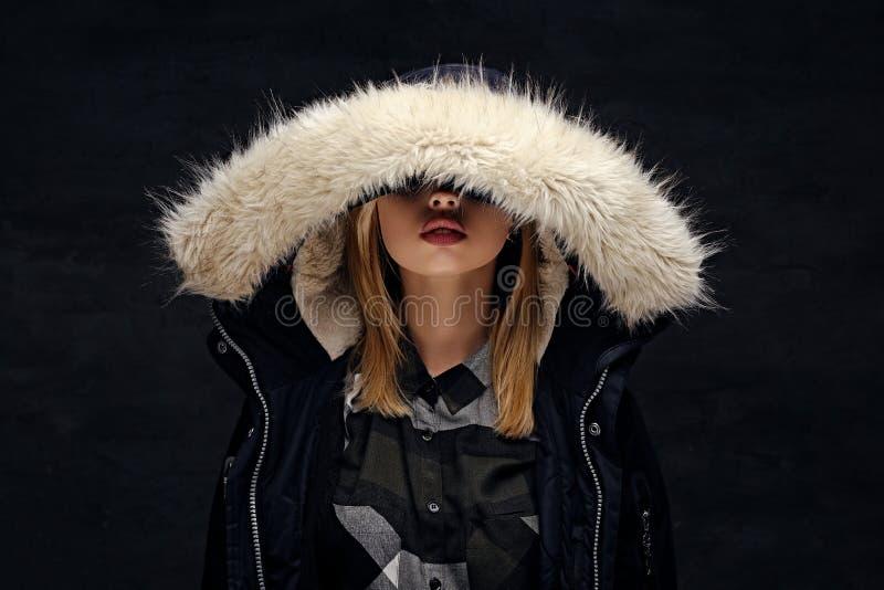 妇女在有深毛皮敞篷的冬天夹克穿戴了 免版税库存图片