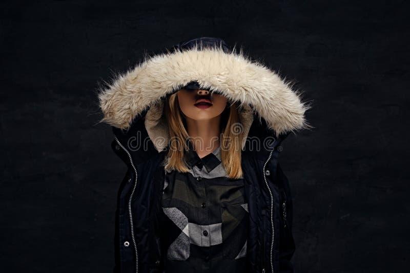 妇女在有深毛皮敞篷的冬天夹克穿戴了 免版税库存照片