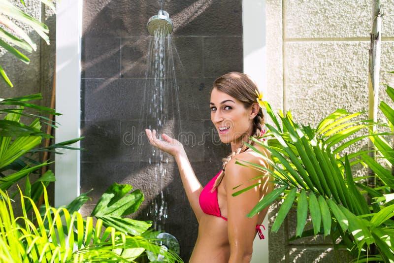 妇女在有热带的庭院里阵雨 免版税库存图片