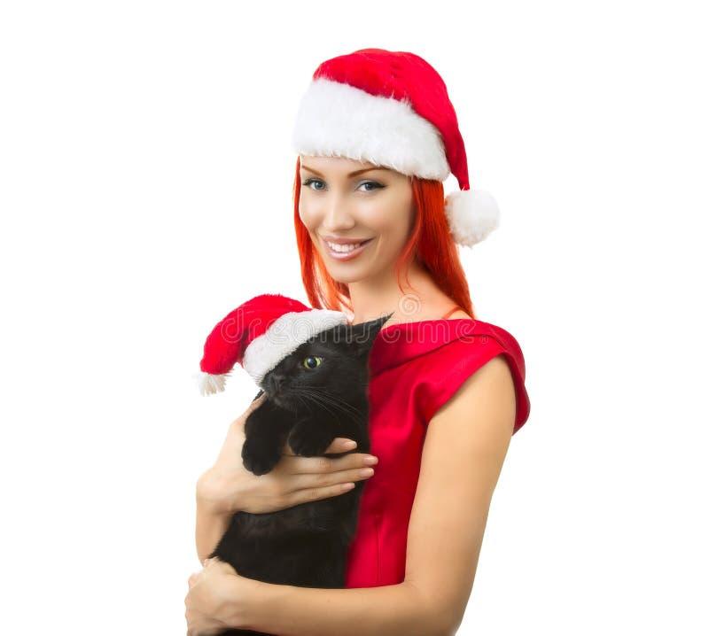妇女在有猫的圣诞老人-逗人喜爱的圣诞节猫, Ch圣诞老人帽子 免版税图库摄影