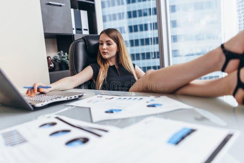 妇女在有腿的书桌在运作的桌坐分析公司的财政统计的膝上型计算机 免版税库存图片