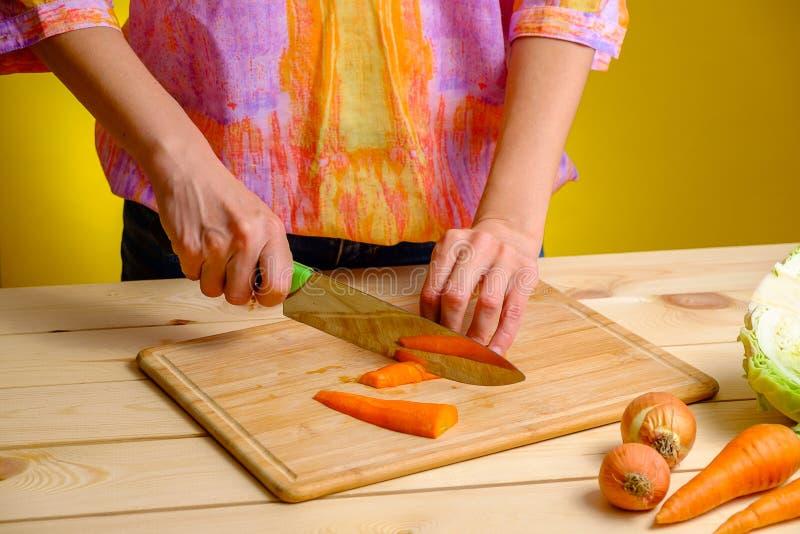 妇女在木板和菜的切口红萝卜在她附近 免版税库存照片