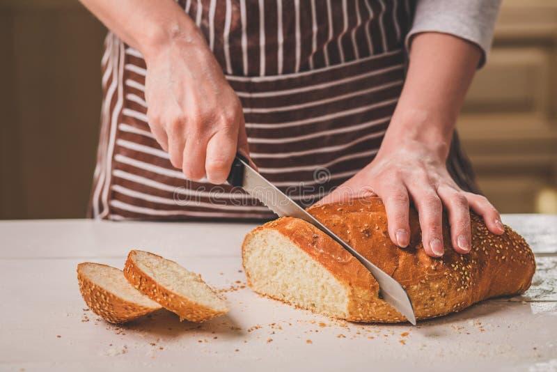 妇女在木板的切口面包 细菌学家 面包生产 免版税图库摄影