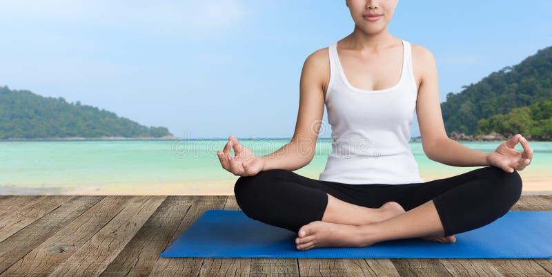 妇女在木阳台海滩的凝思瑜伽 库存照片