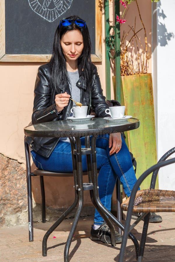 妇女在桌上坐街道和饮用的咖啡 免版税库存图片