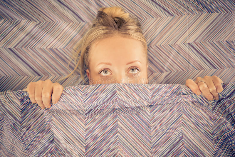 妇女在毯子下的床上 免版税库存照片