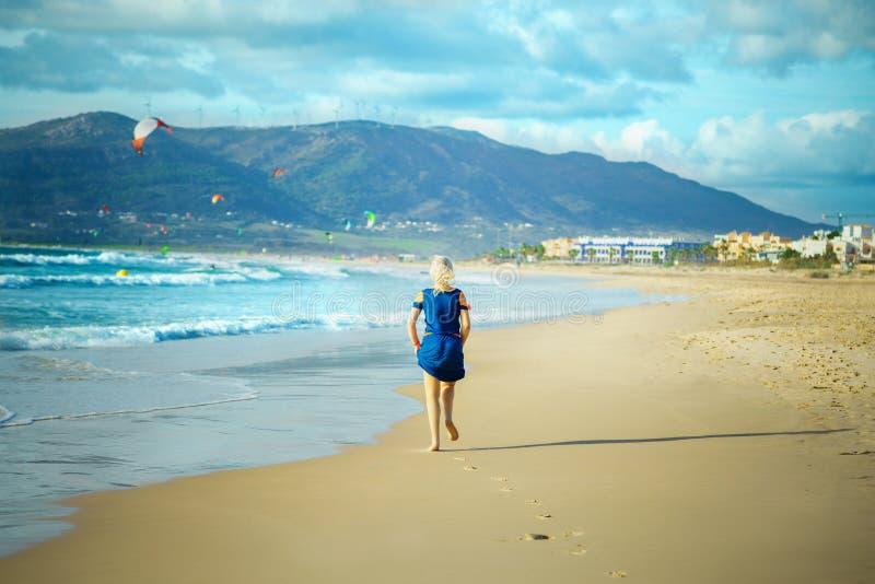 妇女在沙滩跑 免版税库存图片