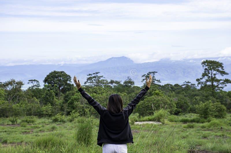 妇女在泰国举他们的胳膊看山和树在Phu Hin荣Kla国立公园,碧差汶府 免版税图库摄影