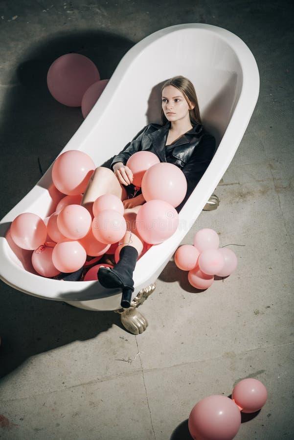 妇女在浴放松 在泡末浴木盆的党气球 在秋天外套的时装模特儿 卫生学和温泉治疗 有 库存图片