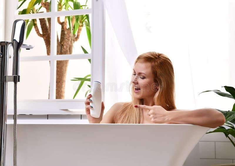 妇女在浴缸的采取浴近开放卫生间窗口和有软的阵雨的洗涤手形成胶冻奶油色化妆水 免版税库存图片