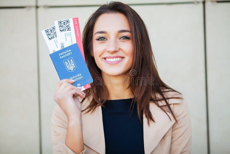 ?? 妇女在海外护照的藏品两机票在机场附近 图库摄影