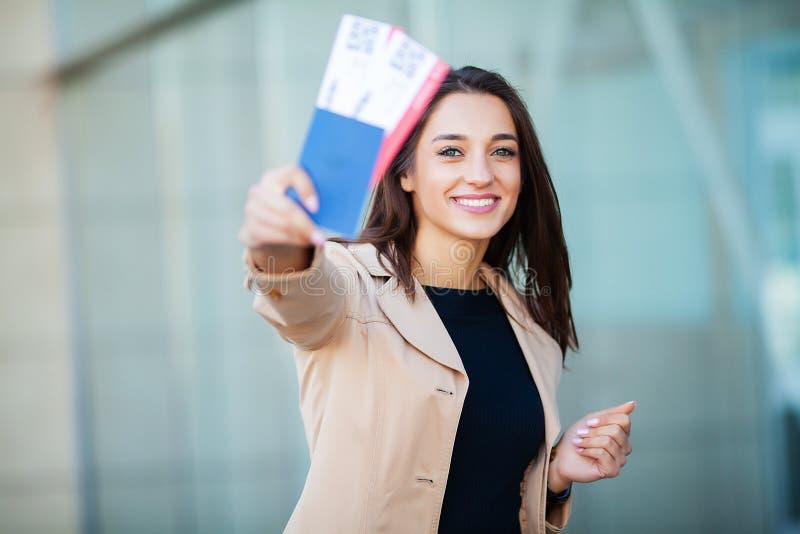 ?? 妇女在海外护照的藏品两机票在机场附近 免版税库存图片