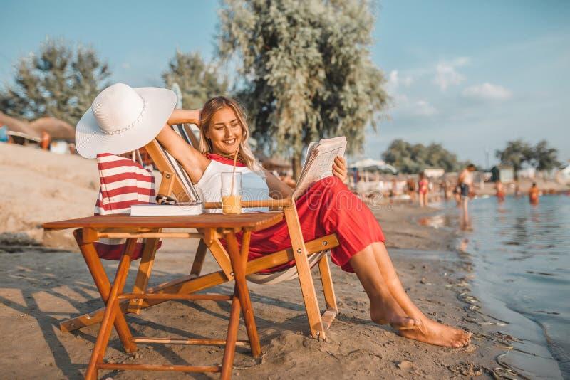 妇女在海滩的读书报纸 库存图片