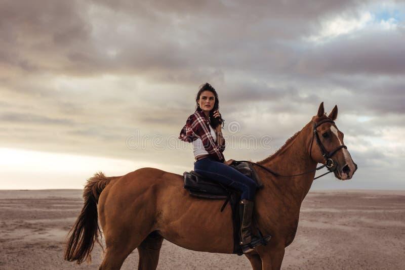 妇女在海滩的马骑术在晚上 库存照片