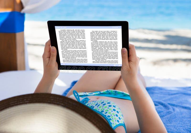 妇女在海滩的读书e书 免版税图库摄影