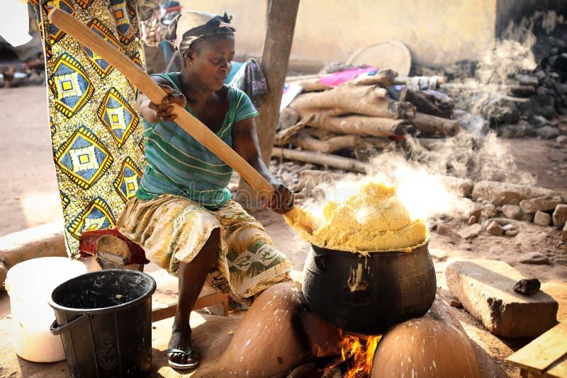 妇女在温尼巴,加纳准备玉米粥 库存图片