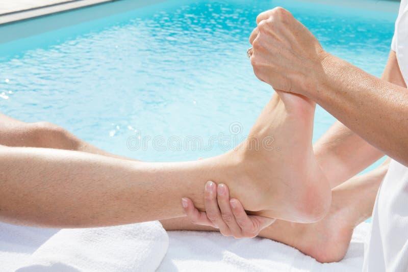 妇女在温泉的水池附近递按摩在一张医疗桌上的人脚 图库摄影