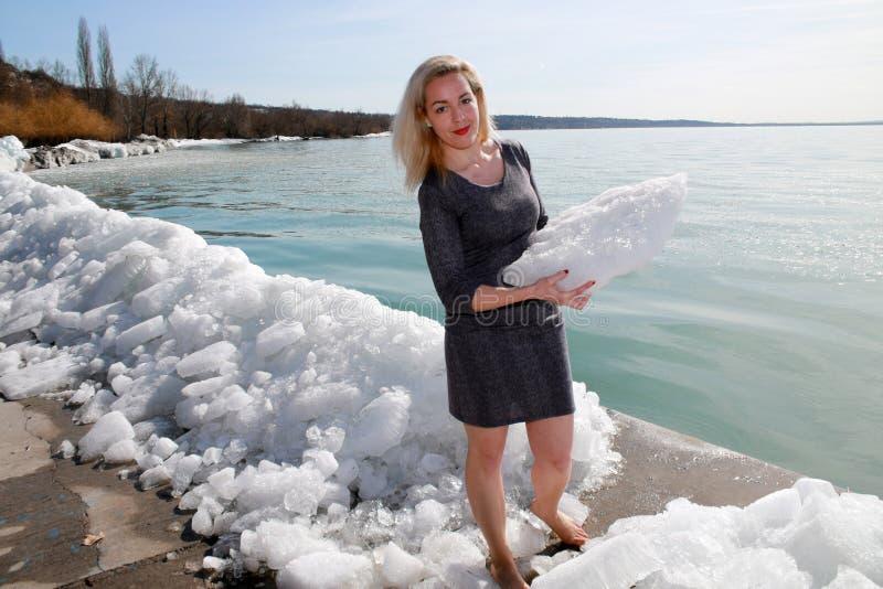妇女在湖障碍冰赤足站立  免版税库存图片