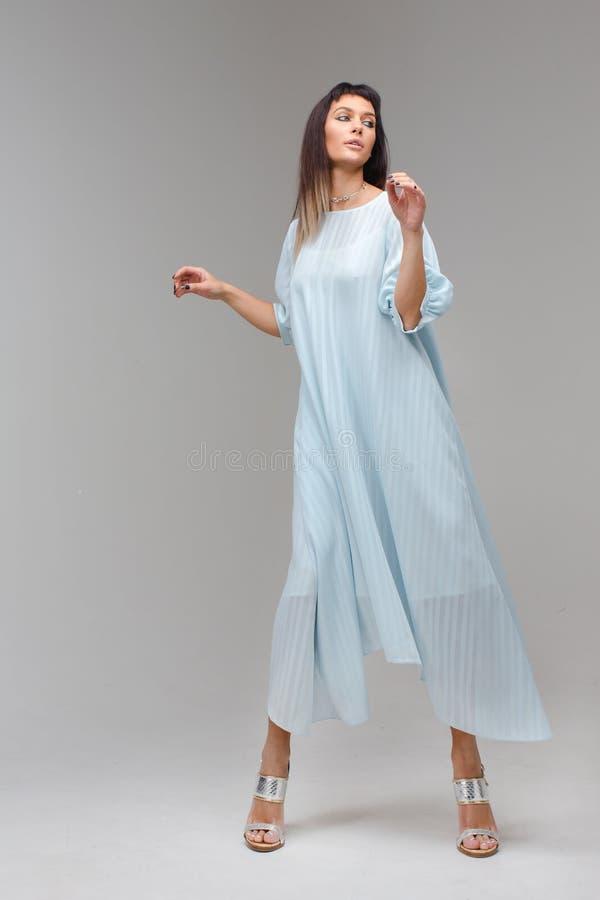 妇女在演播室做在轻的长的蓝色礼服的步 免版税库存照片