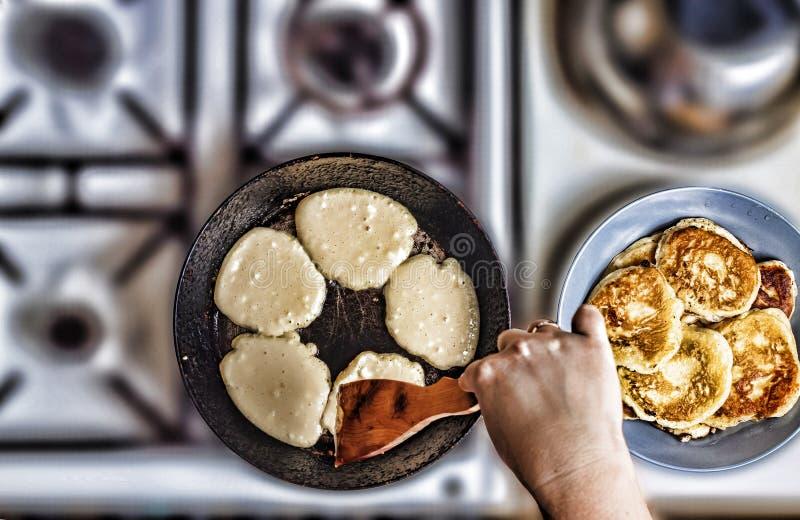 妇女在煎锅的油炸物薄煎饼 库存照片