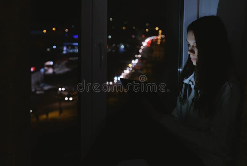 妇女在片剂计算机上的浏览网坐窗台在黑暗的夜 路背景 库存图片