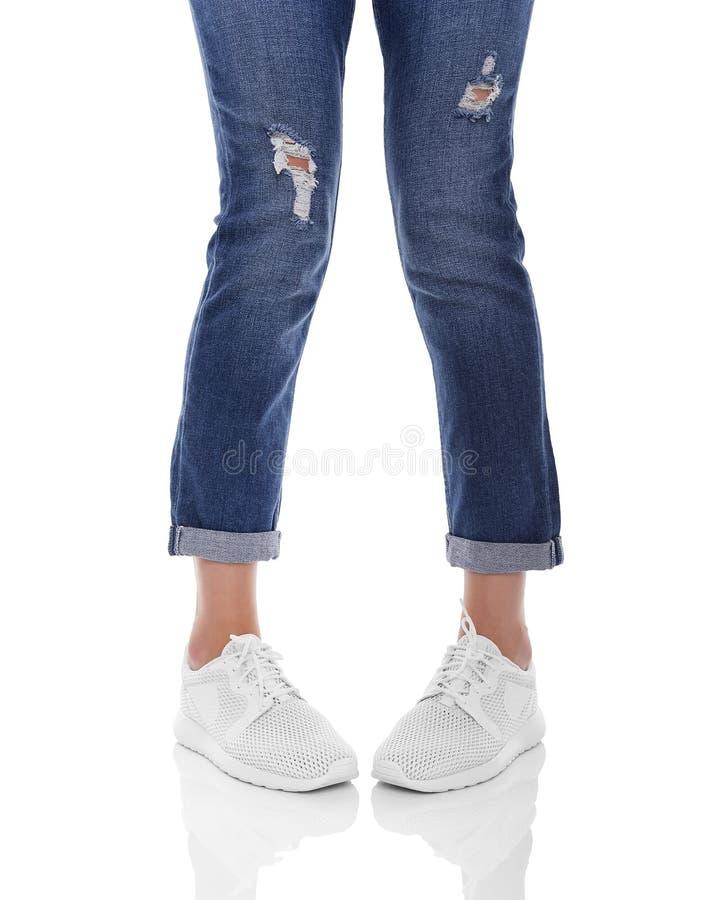 妇女在牛仔裤和运动鞋的` s腿 免版税库存图片