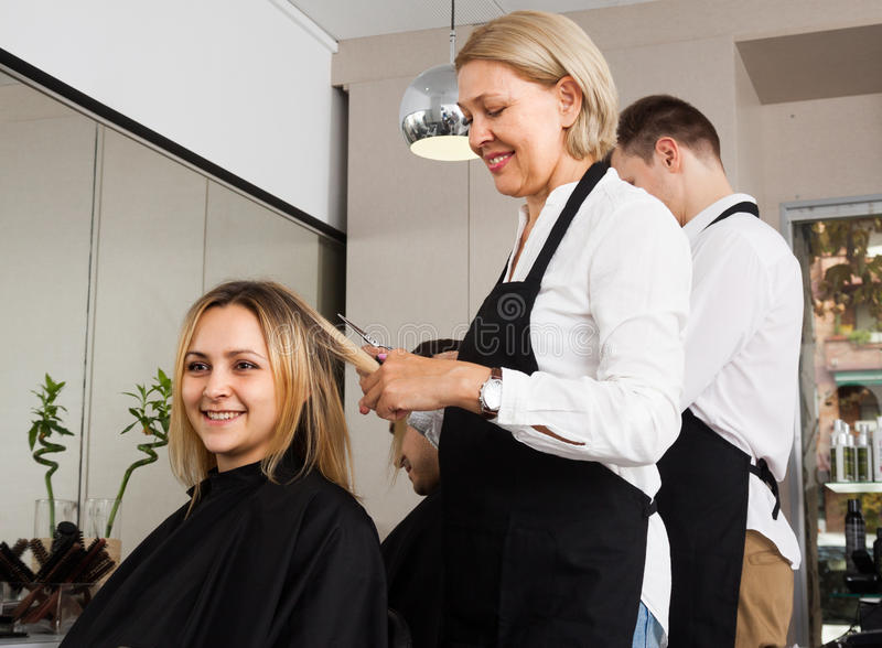 妇女在理发交谊厅的美发师裁减图片