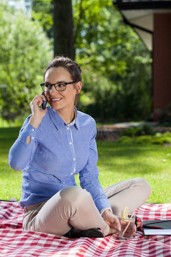 妇女在电话谈话在庭院里 免版税图库摄影