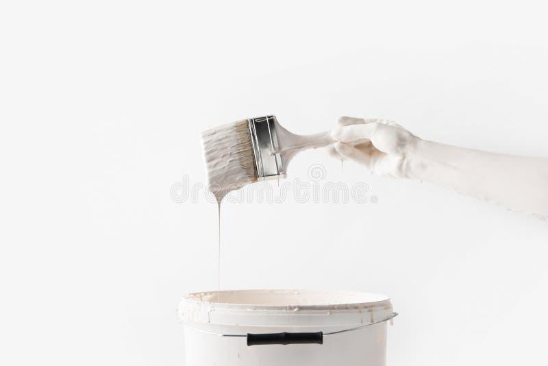 妇女在白色油漆的藏品刷子的播种的图象在桶上 免版税库存照片