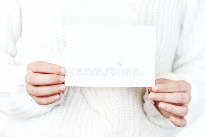 妇女在白色的` s手特写镜头编织了拿着白纸卡片的毛线衣 贺卡大模型 Chritsmas冬天 库存照片