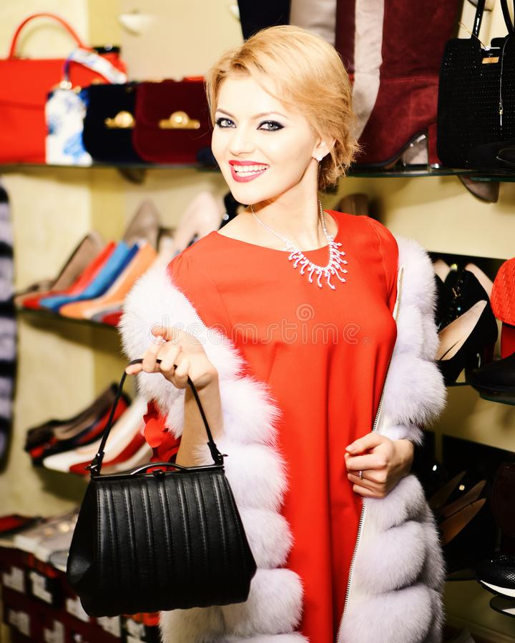 妇女在白色皮大衣穿戴了在时尚商店 免版税图库摄影