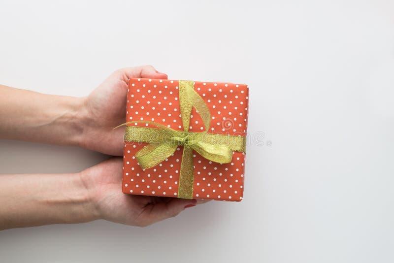 妇女在白色背景递拿着红色礼物盒被隔绝 顶视图,平的位置 Copyspace 免版税图库摄影