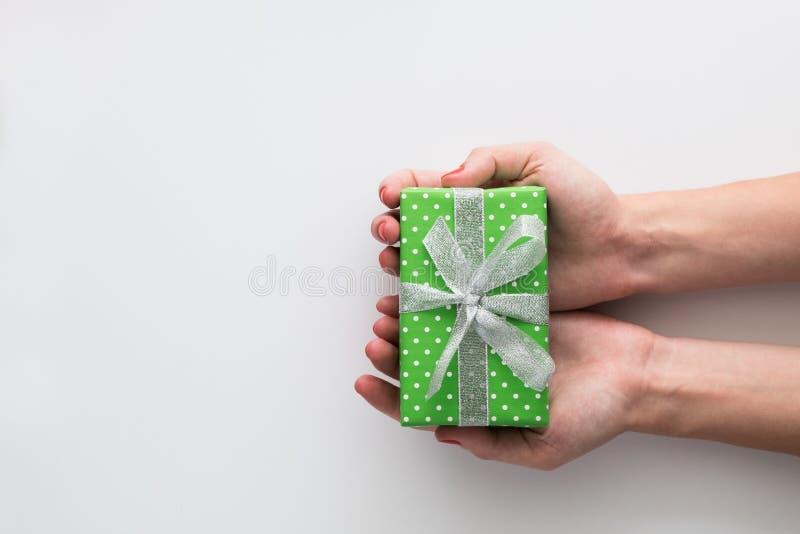 妇女在白色背景递拿着绿色礼物盒被隔绝 顶视图,平的位置 Copyspace 免版税库存照片