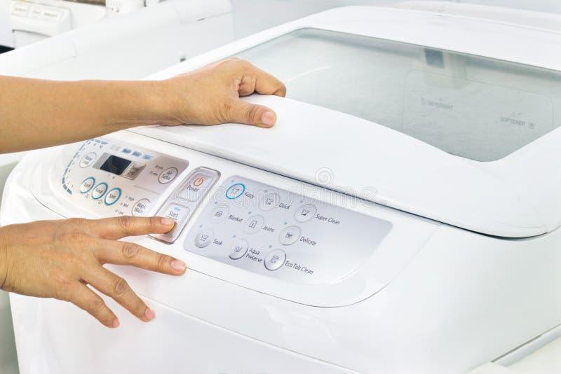 妇女在白色洗衣机的按钮开始 库存图片