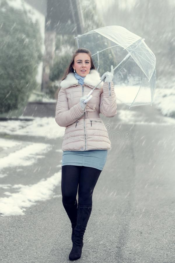 妇女在的一把伞下降雪 图库摄影