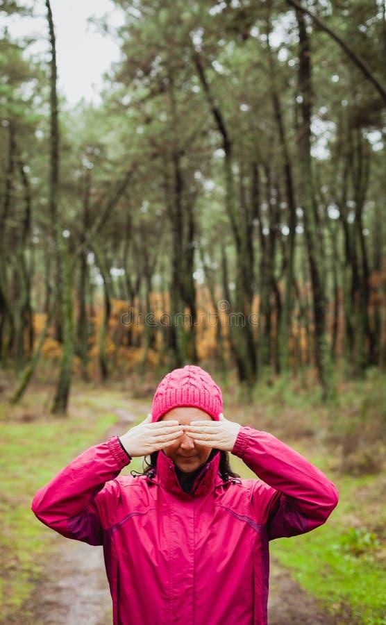 妇女在盖她的眼睛的森林里 免版税库存图片