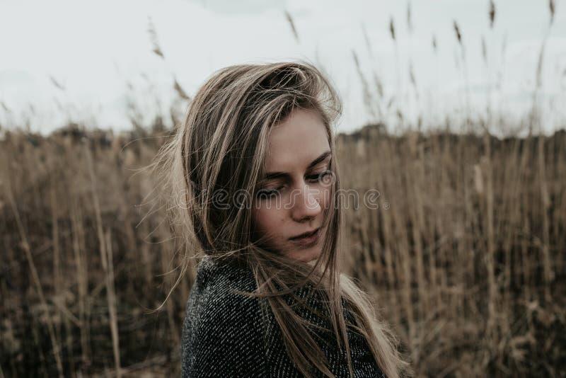 妇女在看下来在她的肩膀的羊毛外套穿戴了 背景纸莎草 室外 中景 免版税库存照片