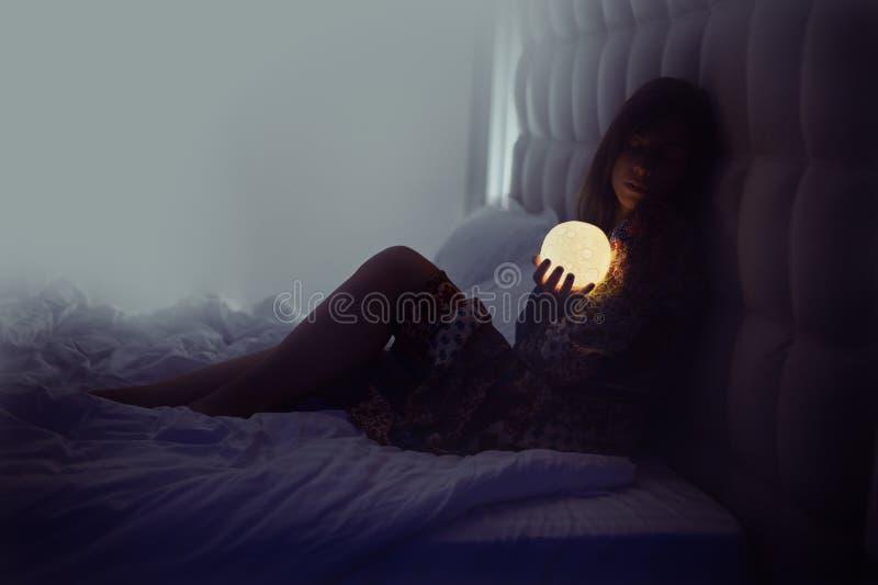 妇女在看月亮的床上 免版税库存图片