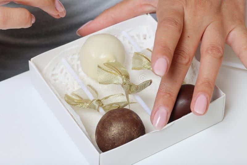 妇女在礼物盒投入蛋糕流行音乐 剪鞭子糖果 糖果用丝带装饰 库存图片