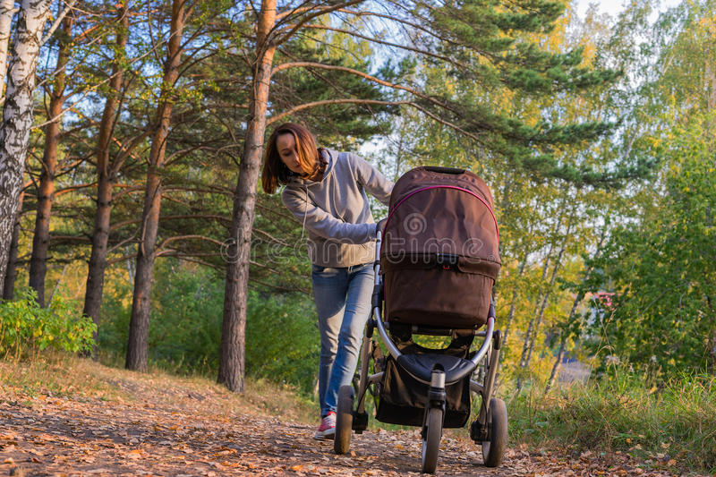 妇女在秋天森林里滚动婴儿推车 免版税库存照片