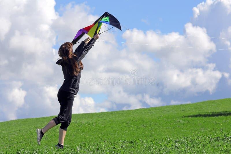 妇女在秋天要飞行一只风筝 库存图片