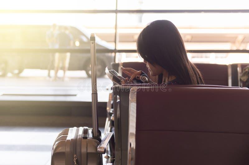 妇女在移动电话的检验飞行数字在机场 库存照片