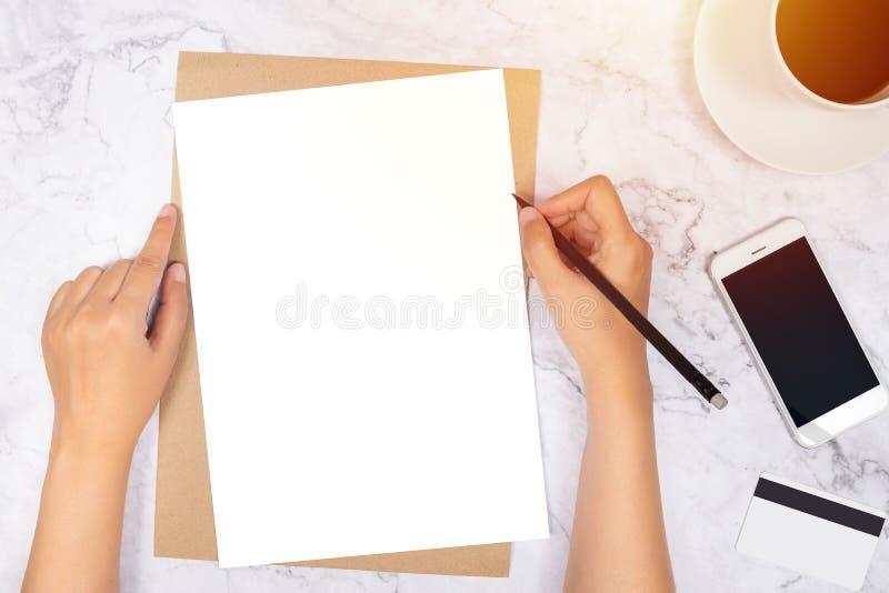 妇女在空白的白皮书的手文字平的位置在与铅笔,手机,信用卡的包装纸信封 库存图片
