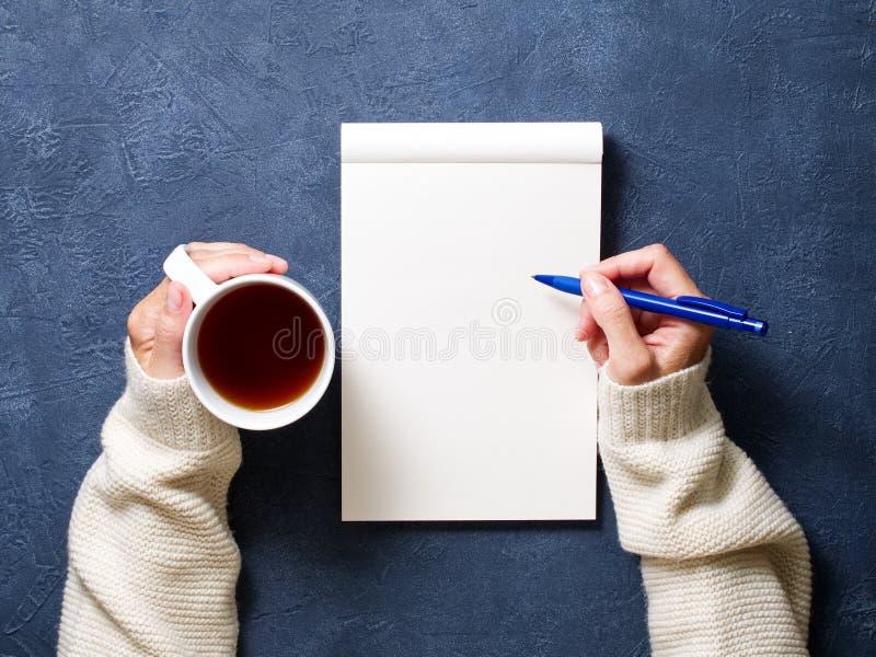 妇女在笔记本写在深蓝桌,在拿着铅笔,茶的衬衣的手,写生簿图画,顶视图 免版税库存图片