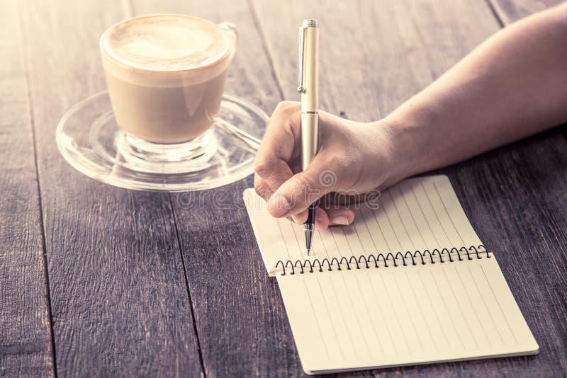 妇女在笔记本的手文字在木桌 免版税图库摄影