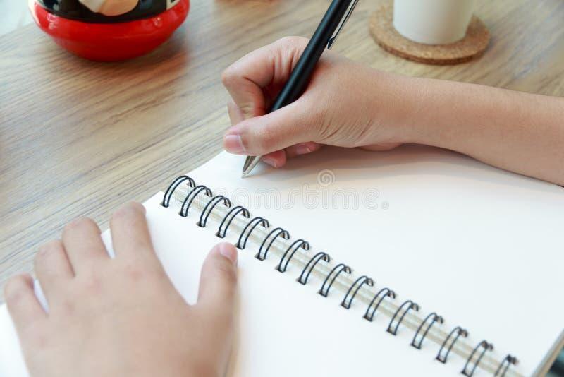 妇女在笔记本纸的手文字与在木书桌上的一支笔我 免版税库存照片