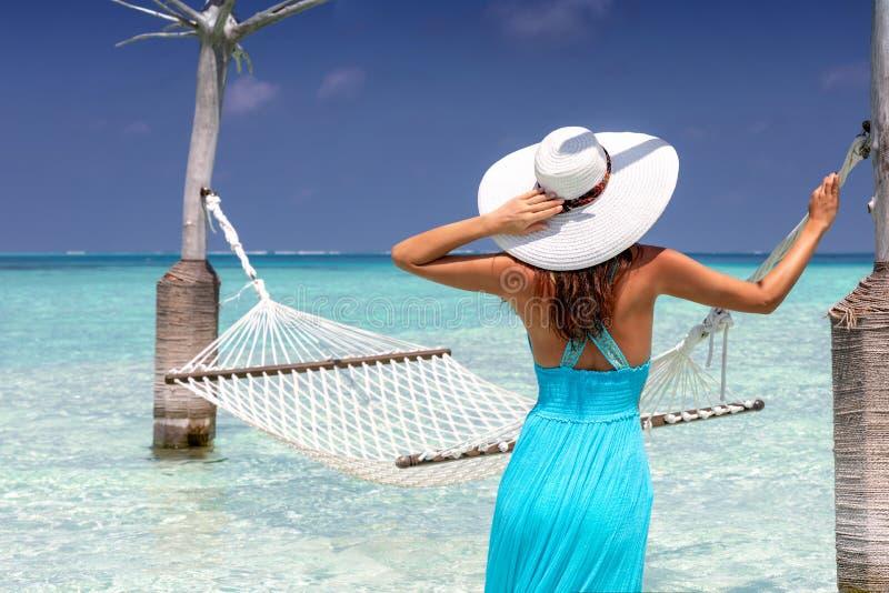 妇女在绿松石,热带水的一个吊床前面站立 免版税库存图片