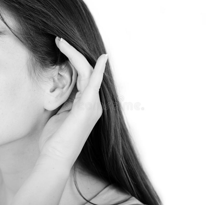 妇女在耳朵附近握她的手并且听 免版税库存照片